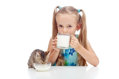 Drinking milk with my best friend - little girl and kitten enjoying dairy product photo