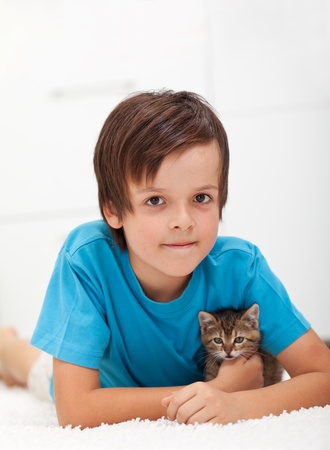 Young boy holding his kitten - laying on the floor photo
