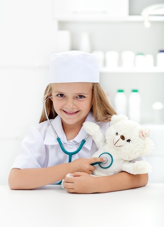 role play: Little girl playing veterinary - examining her toy with stethoscope