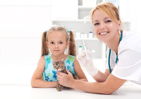 Little girl and kitten at the veterinary - getting a vaccine for a new pet photo