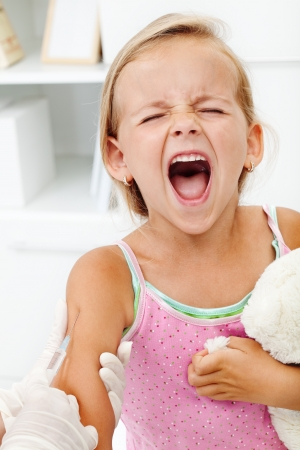 tetanus: Distressed little girl getting an injection or vaccine - shouting hysterical Stock Photo