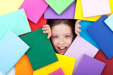 mucha gente: Descubrir el maravilloso mundo del conocimiento - chica joven sorprendida saliendo de debajo de coloridos libros