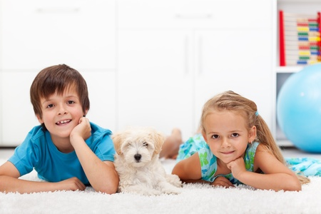 big girl: Happy kids with their pet - a fluffy dog - laying on the floor