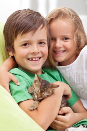 Happy kids holding their new pet - a little kitten asleep in their arms photo