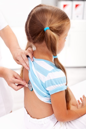 examine: Little girl being checked with a stethoscope at the doctors - closeup