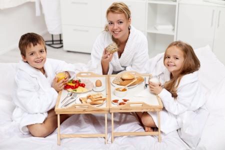 Szczęśliwa rano - kobieta i dzieci posiadające lekką brekfast w łóżku
