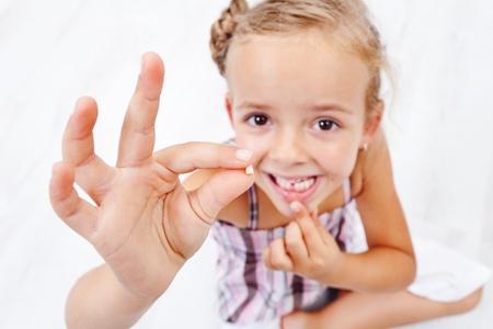 Dziewczynka wykazujące jej pierwszy wypadł ząb mleczny