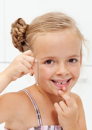 tooth extraction: Happy little girl with her first missing milk tooth on a string