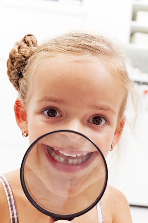 lost child: Happy little girl with missing milk tooth showing the gap through magnifier
