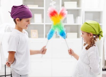huis opruimen: Een voor allen en allen voor een nette kamer - kinderen met stoffer borstels, richten zich op het meisje Stockfoto