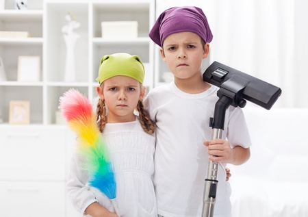 clean room: Why do we have to clean our room - upset kids with cleaning utensils Stock Photo