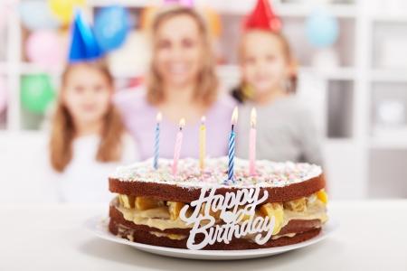 fiesta familiar: El hogar hizo la torta de cumplea�os feliz con las chicas de fiesta en el fondo