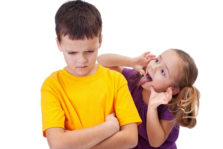 spiteful: Young girl mocking angry boy - isolated