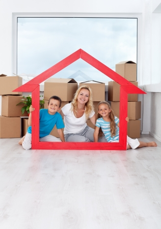 enjoy space: Happy family in their new home laughing by a large house shaped frame Stock Photo