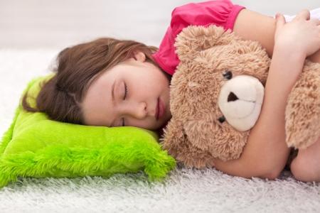 niño durmiendo: Chica joven que toma una siesta tranquila con su osito de peluche favorito