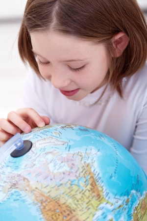 Learning about the world - young girl with earth globe photo