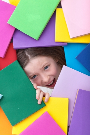 too much: Covered by too much information - young girl emerging from beneath books Stock Photo
