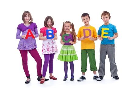 Młodzi uczniowie stojących w rzędzie trzyma litery ABC - wyizolowanych z odrobiną cienia