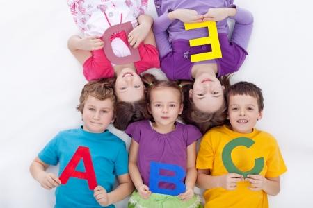 school teens: Grupo de ni�os que sostienen las letras del alfabeto - de vuelta a la escuela juntos Foto de archivo
