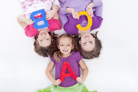 Girls holding A B C letters - laying on the floor photo