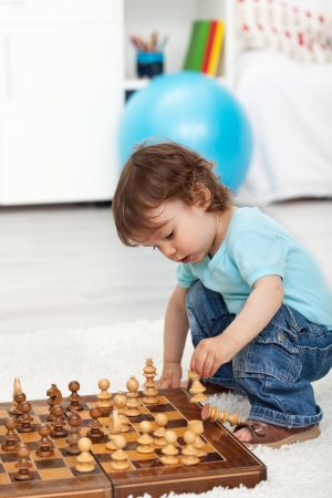 Toddler boy crouching and playing with chess pieces photo