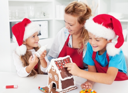 Making a gingerbread cookie house with the kids at christmas time photo
