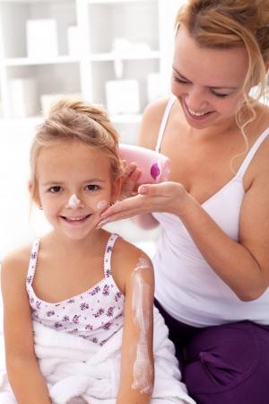 Rytuał piękności - mała dziewczynka i matka stosując balsam do ciała po kąpieli
