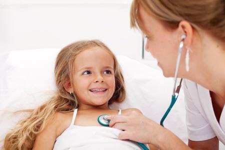 enfant malade: Petite fille dans le lit avec un bilan de sant� - p�diatre �coute avec un st�thoscope Banque d'images