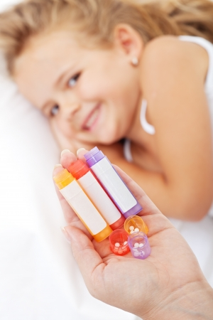 Medicación homeopática en mano de la mujer - niña sonriente en el fondo