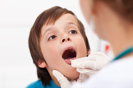 woman mouth open: Say aaah - little boy having his throat examined by health professional - closeup