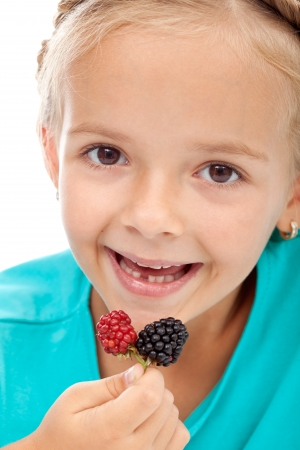 Little girl eating blackberries - closeup photo