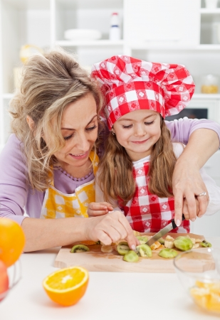 Woman and little girl making fresh fruits snack together - healthy eating concept photo