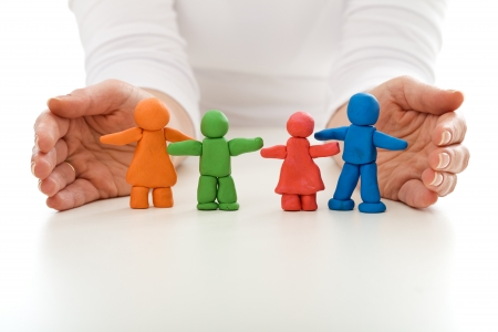 protect family: Clay people family protected by woman hands - life insurance concept Stock Photo