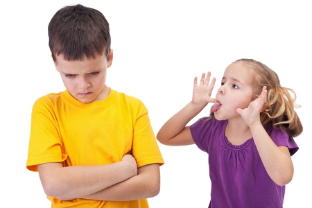 hassle: Mocking and teasing among children - girl taunting upset boy, isolated