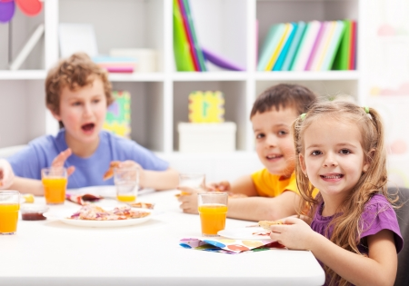 Childhood friends eating together in kids room photo