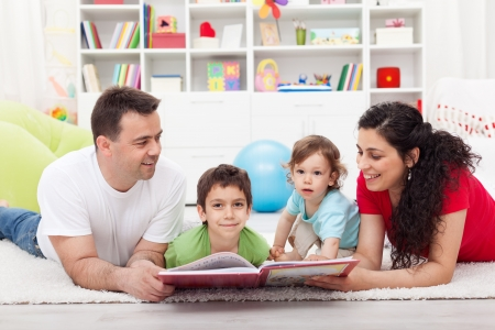 child learning: Young family story time with the kids - laying on the floor together