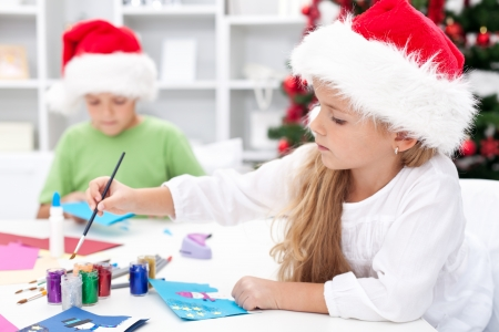 Kids making christmas greetings wearing santa hats