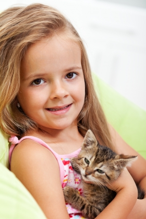 Little girl holding her kitten - shallow depth of field, closeup
