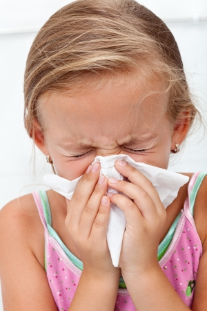 gir: Little gir blowing her nose in a great effort - closeup Stock Photo
