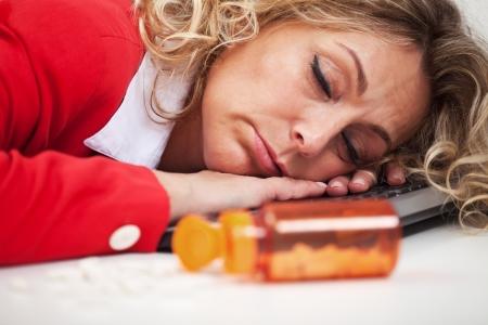 Wyczerpanie - kobieta śpi na klawiaturze komputera z pigułek na pierwszym planie Zdjęcie Seryjne