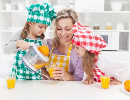 Girls and their mother making fresh orange juice in the kitchen photo