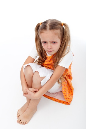 tantrum: Extremely unhappy little girl sitting and crying - on white background