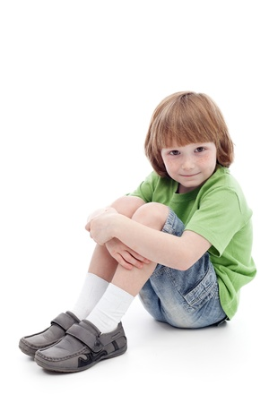 Adorable small boy sitting on the floor - isolated Zdjęcie Seryjne
