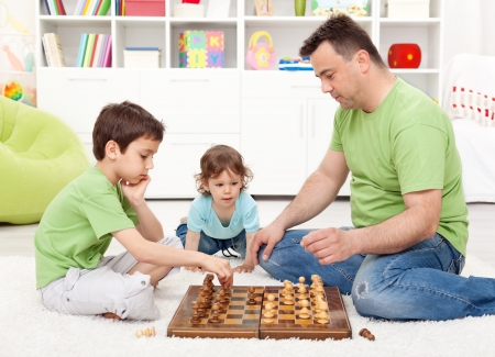 Boys playing chess with their father in the kids room - focus on smaller child photo
