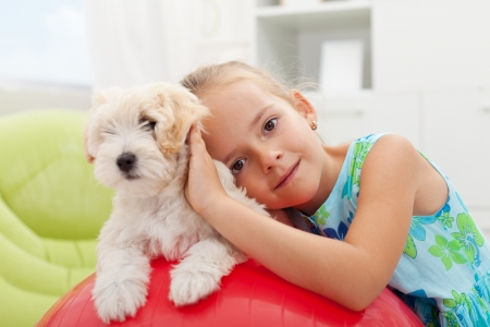 Little girl playing with her small fluffy dog at home photo