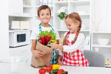 Dzieci rozpakowaniu zakupy w kuchni - co świeże sałatki warzywa Zdjęcie Seryjne