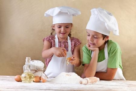 Bambini con cappelli da cuoco preparano pasta tha torta - miscelare ingredienti