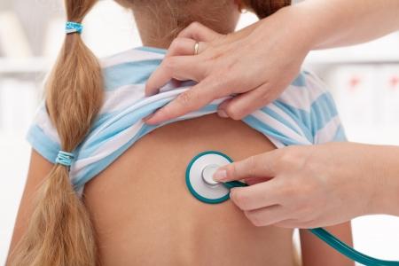 pediatra: Niña en el doctor - área pulmonar examinado con el estetoscopio