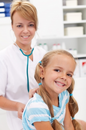 patient safety: Little girl smiling at the doctor - back after recovery for a checkup