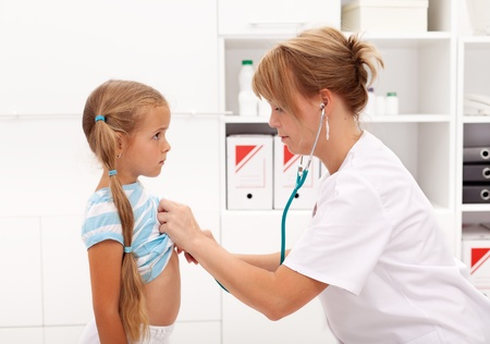 examine: Little girl at the doctor being examined with stethoscope